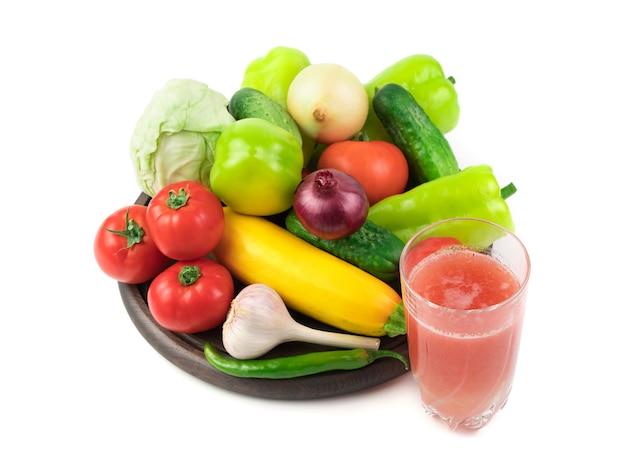 Szklanka soku ze świeżych warzyw i duży wybór świeżych warzyw na okrągłej tacy.