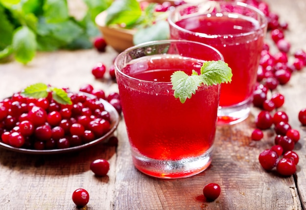 Szklanka soku żurawinowego ze świeżymi jagodami na drewnianym stole