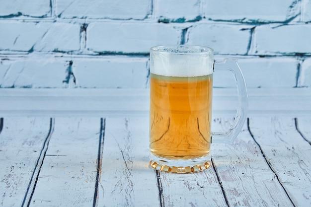 Szklanka spienionego piwa na niebieskim stole.