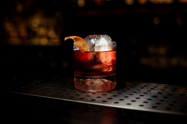 Szklanka świeżego i mocnego koktajlu whisky ozdobiona skórką pomarańczową