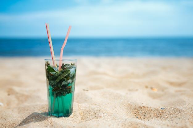 Szklanka świeżego koktajlu mojito na plaży