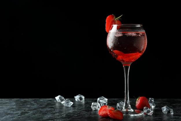 Szklanka świeżego koktajlu truskawkowego na czarnym stole smokey
