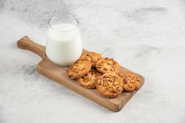Szklanka świeżego mleka i smaczne ciastka na drewnianej desce do krojenia.