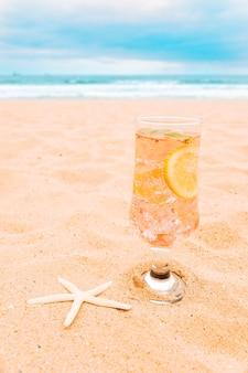 Szklanka świeżego napoju z plasterkami cytrusów i rozgwiazdy