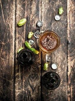 Szklanka świeżego piwa z butelkami i korkiem na drewnianym stole.