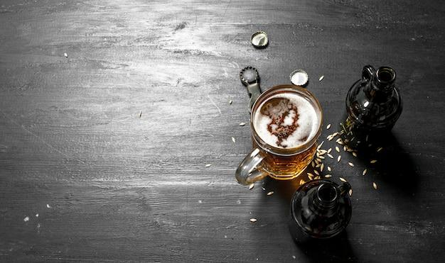 Szklanka świeżego piwa z butelkami i otwieraczem. na czarnej tablicy.