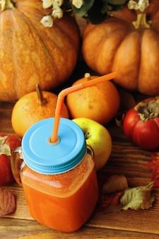 Szklanka świeżego smoothie z dyni na drewnianym tle dojrzałe dynie jabłka opadają liście i kwiaty ...