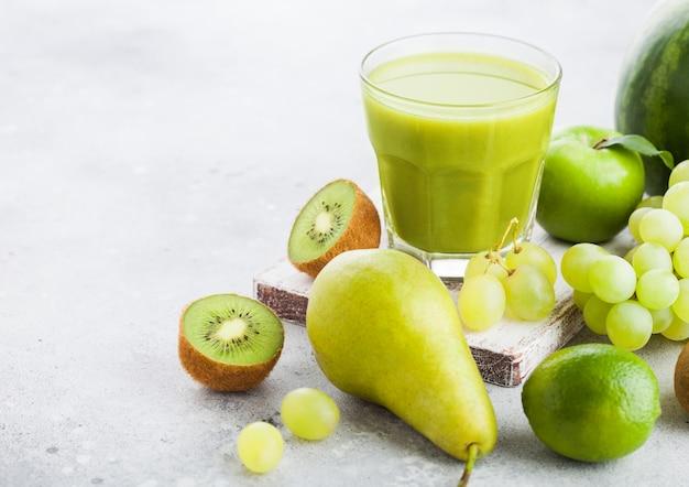 Szklanka świeżego smoothie z ekologicznymi zielonymi owocami w kamiennej kuchni. gruszka i winogrona z kiwi i limonką z jabłkiem i arbuzem
