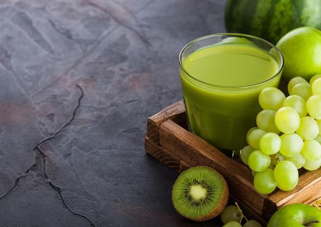 Szklanka świeżego smoothie z organicznymi zielonymi stonowanymi owocami w białym pudełku na kamiennej kuchni. gruszka i winogrona z kiwi i limonką z jabłkiem.