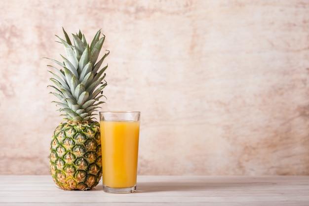 Szklanka świeżego soku ananasowego z surowymi owocami na drewnianym