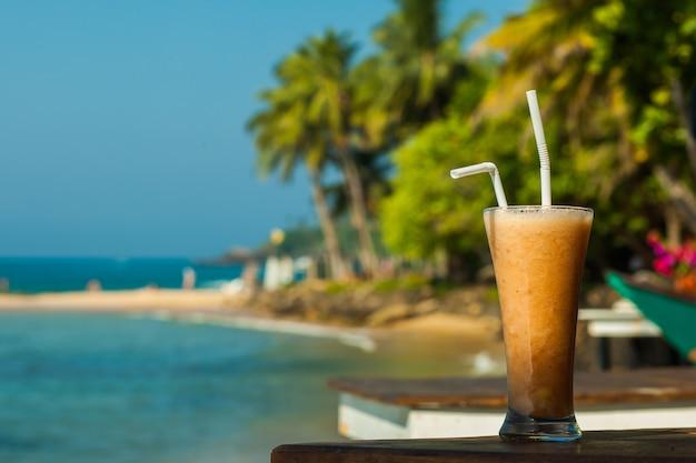 Szklanka świeżego soku owocowego nad morzem i palmami