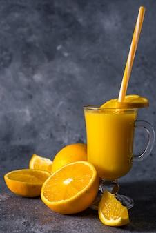 Szklanka świeżego soku pomarańczowego, dojrzałych owoców pomarańczy i plasterków