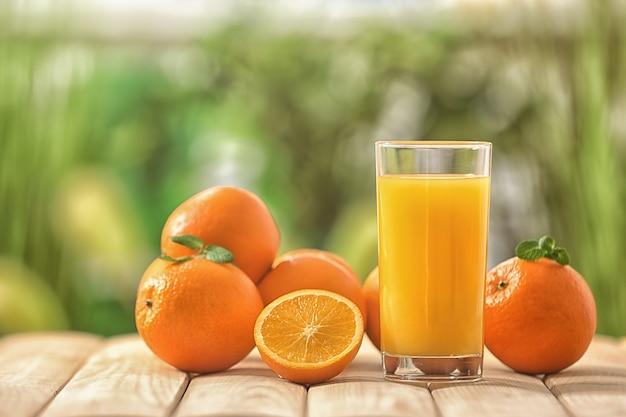 Szklanka świeżego soku pomarańczowego na drewnianym stole na zewnątrz