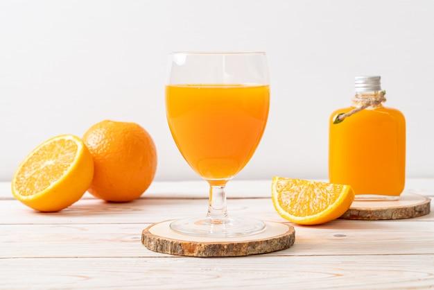 Szklanka świeżego soku pomarańczowego z pomarańczami
