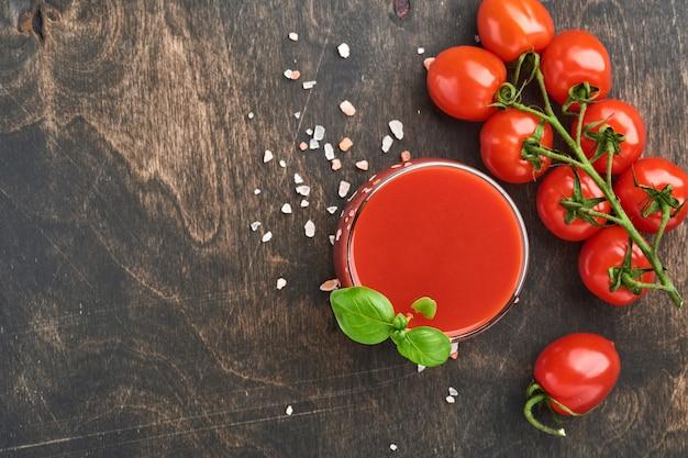 Szklanka świeżego soku pomidorowego, soli, bazylii i pomidorów na drewnianym stojaku na starym drewnianym tle. widok z góry z miejsca na kopię.