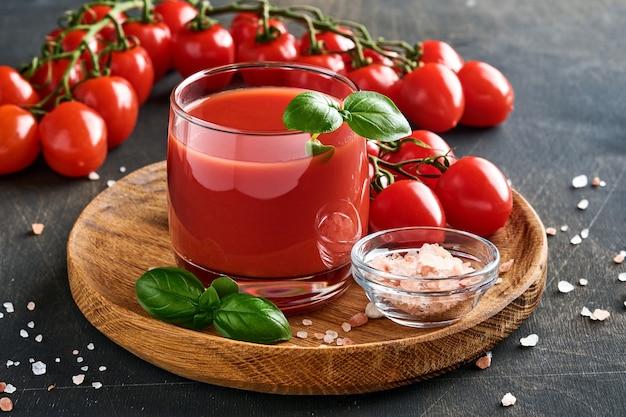 Szklanka świeżego soku pomidorowego, soli, bazylii i pomidorów na drewnianym stojaku na starym drewnianym tle. z miejscem na kopię.