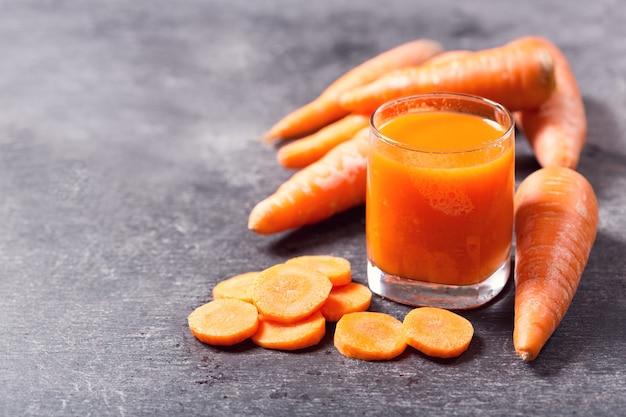 Szklanka świeżego soku z marchwi z warzywami na ciemny