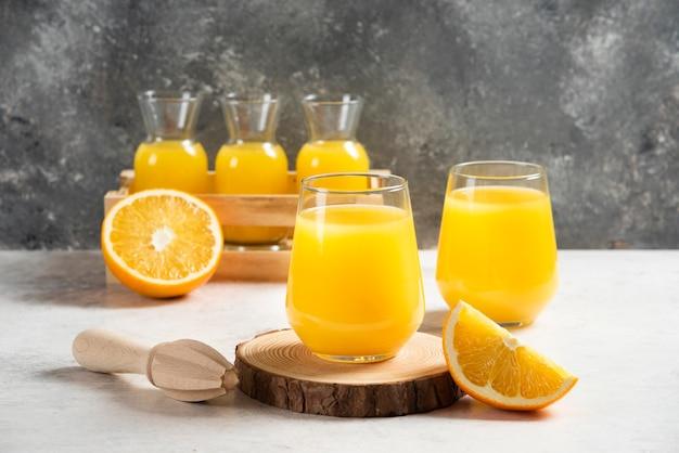 Szklanka świeżego soku z plasterkami pomarańczy.
