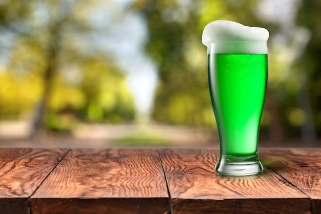Szklanka świeżego zimnego zielonego piwa z dodatkową pianką na drewnianym stole z niewyraźnymi zielonymi liśćmi latem na naturalnym tle z bokeh, kopia przestrzeń. koncepcja happy st patrick's day.