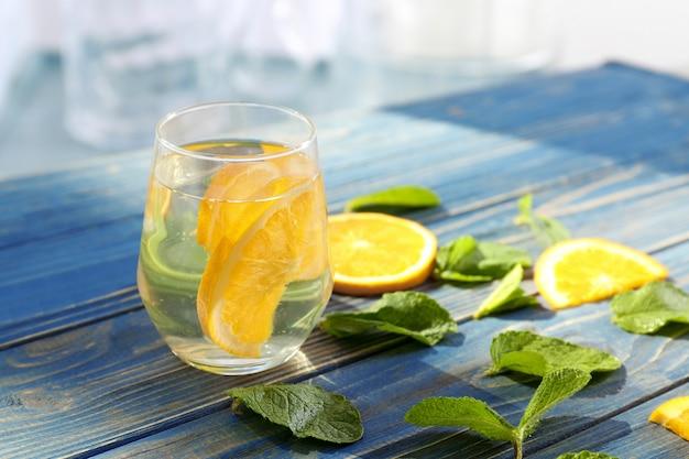Szklanka świeżej lemoniady pomarańczowej na drewnianym stole