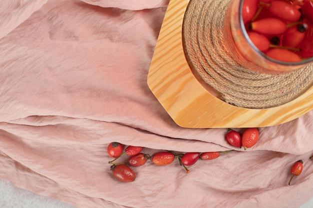 Szklanka świeżej lemoniady z owocami dzikiej róży na drewnianym talerzu.