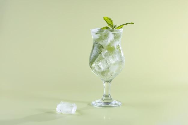Szklanka świeżej wody sodowej z kostkami lodu i miętą