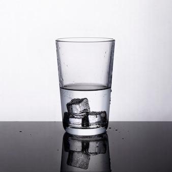 Szklanka świeżej wody z kostkami lodu