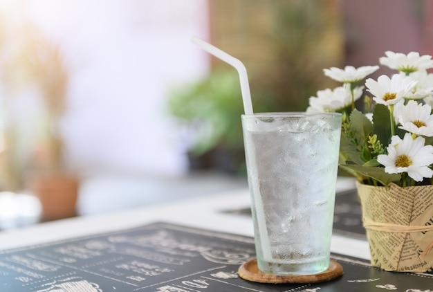 Szklanka świeżej wody z lodem na stole