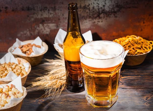 Szklanka świeżo nalewanego piwa i pianka w pobliżu butelki i talerzy z pistacjami, małymi preclami, orzeszkami ziemnymi na ciemnym drewnianym biurku. koncepcja żywności i napojów