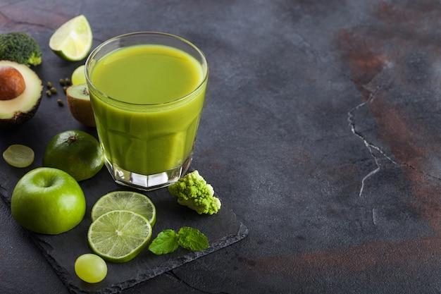 Szklanka świeżych surowych organicznych zielonych owoców i warzyw. awokado, limonka, jabłko, kiwi i winogrona z brokułami i kalafiorem