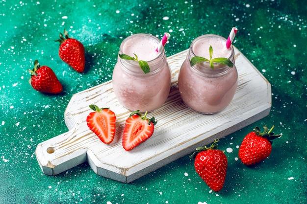 Szklanka świeżych truskawkowych koktajli mlecznych, smoothie i świeżych truskawek, koncepcja zdrowej żywności i napojów.