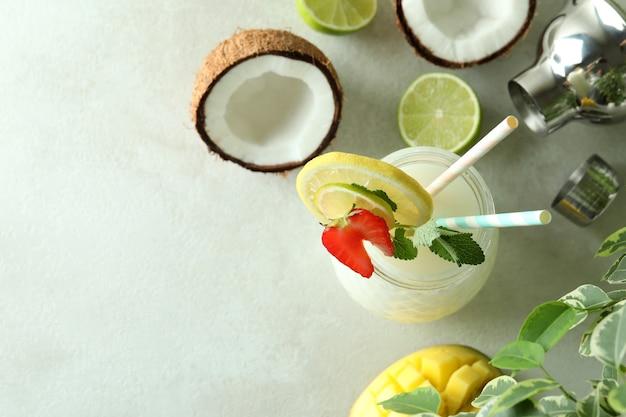 Szklanka tropikalnego koktajlu i składników na białym stole z teksturą