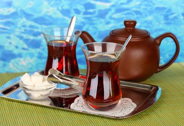 Szklanka tureckiej herbaty i czajnik na kolorowym tle