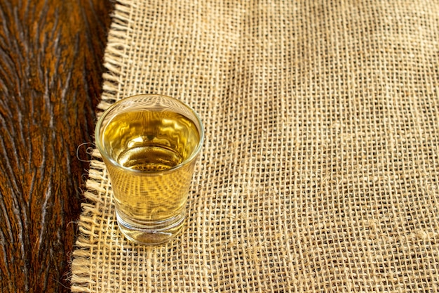 Szklanka typowego brazylijskiego napoju cachaca w jutowej tkaninie i drewnianym stole