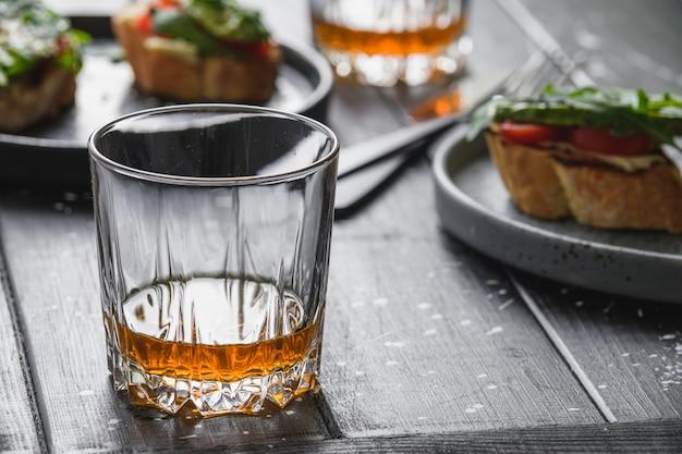 Szklanka whisky i kanapka z awokado.