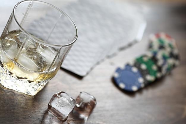 Szklanka whisky i lód na stole do gry z żetonami i kartami