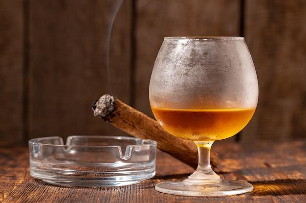 Szklanka whisky i zapalone cygaro w popielniczce