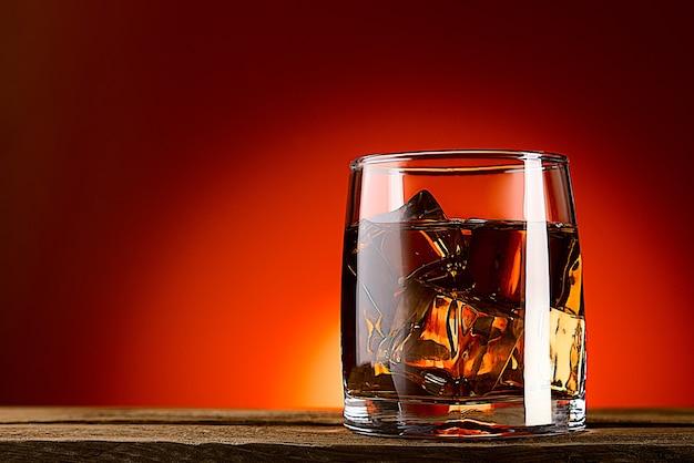 Szklanka whisky lub koniaku i kostki lodu zbliżenie na drewnianym stole czerwone tło z gradientem