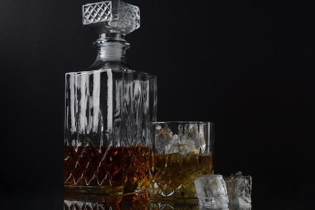 Szklanka whisky z kostkami lodu i kwadratową karafką