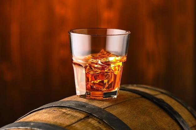 Szklanka whisky z lodem na szczycie beczki