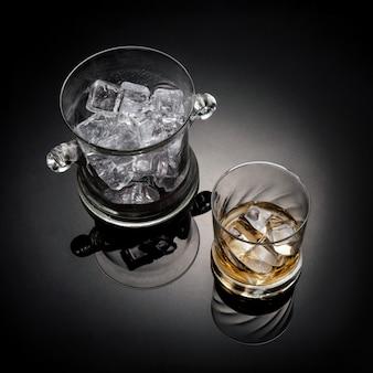 Szklanka whisky ze szklanym wiadrem z lodem