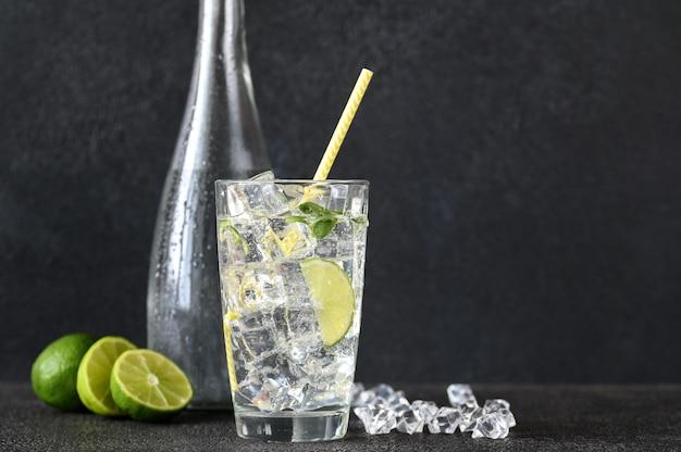 Szklanka wody gazowanej z kostkami lodu i plasterkiem limonki