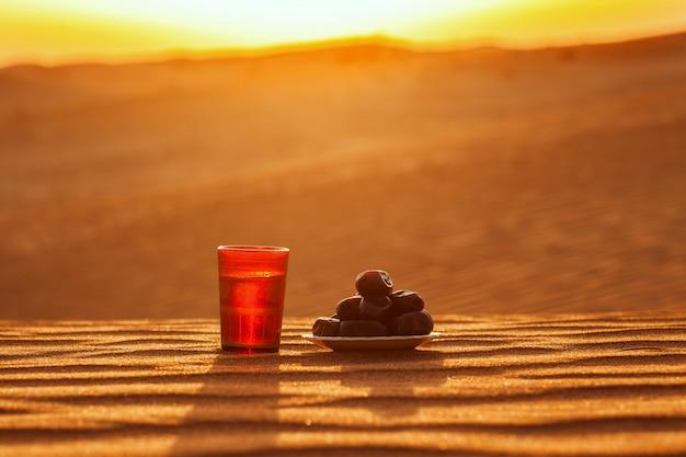Szklanka wody i daty stoją na piasku z widokiem na piękny zachód słońca.