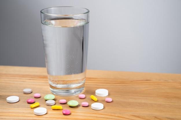 Szklanka wody i kapsułki leku na białym tle.