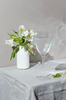 Szklanka wody i kwiatów na stole