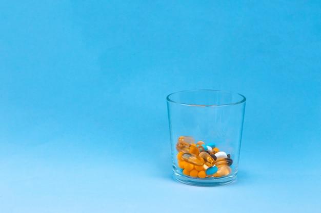 Szklanka wody i pigułki na niebieskim tle z miejsca kopiowania tekstu