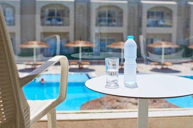Szklanka wody i plastikowa butelka na balkonie przed basenem
