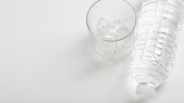 Szklanka wody i plastikowej butelki białej kopii przestrzeni