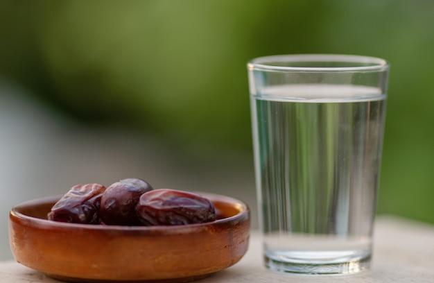 Szklanka wody i suche daktyle iftar na talerzu gotowe do spożycia na czas iftarreligia islamska i ramadan