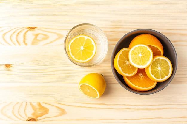 Szklanka wody i talerz cytryn na drewnianym stole widok z góry